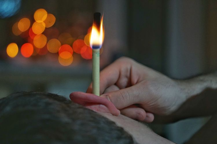 Close-up of hand holding burning paper in man ear