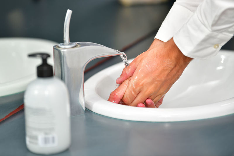 Cropped image of man washing hands in sink