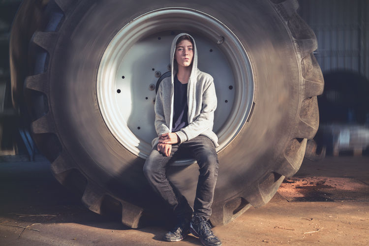 Portrait Young Men Worker Pupil Wheel Workshop Hoodie Cool Serious Young Adult One Person Real People Looking At Camera Front View Lifestyles Leisure Activity Casual Clothing Tranportation Tractor Farmer Model Fashion Cultures Youth Adolescence  Caucasian Round Circle Asphalt