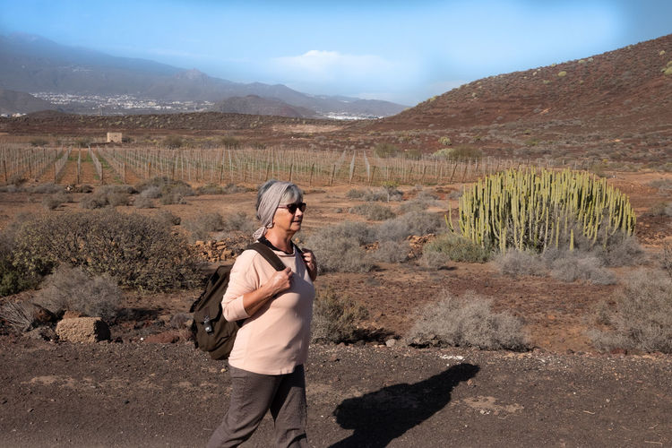 Senior woman with backpack walking on land against mountains