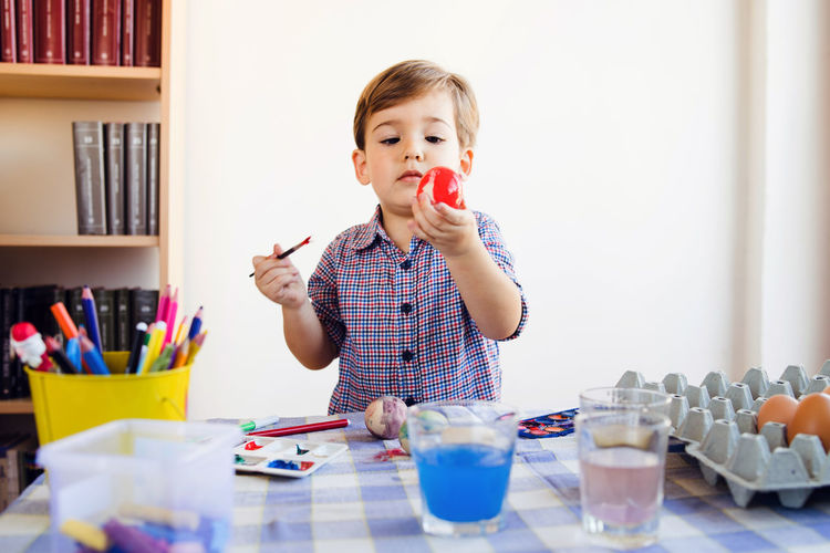 Boy painting easter egg at home