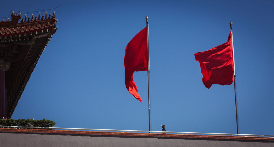 Low Angle View Of Red Flags At Forbidden City Against Clear Blue Sky