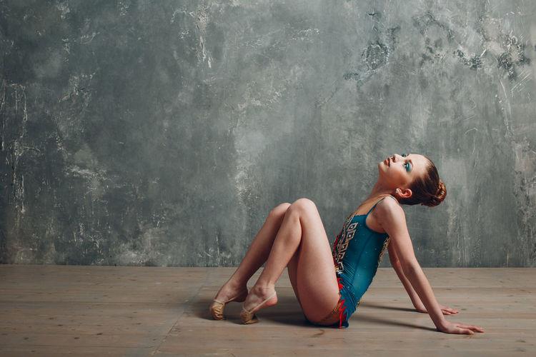 Gymnast girl sitting on hardwood floor against wall