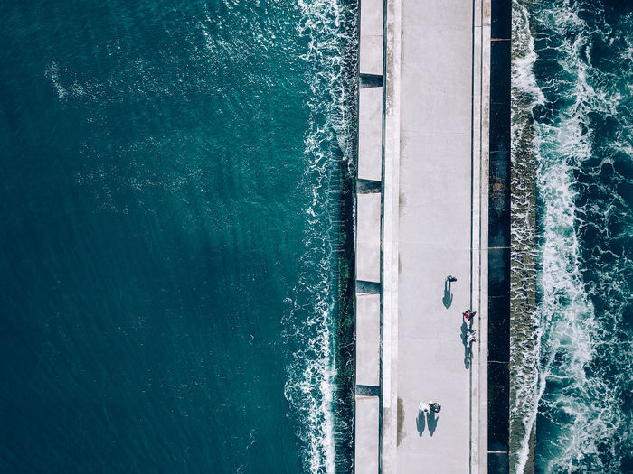 High Angle View Of People Walking On Pier Over Sea During Sunny Day