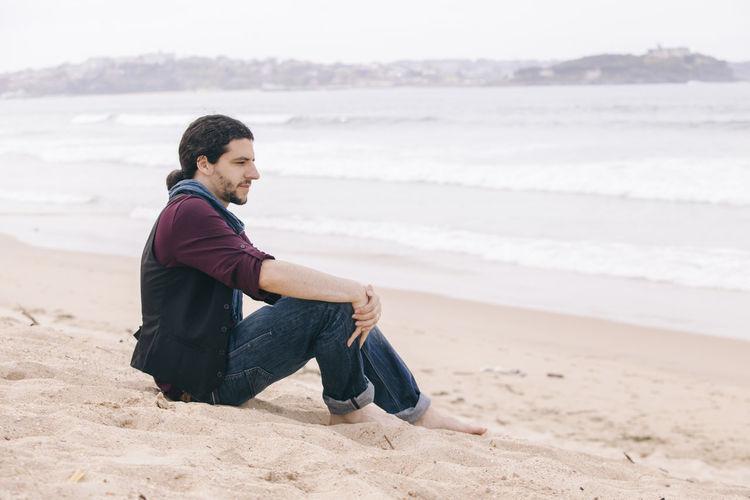 Man sitting at beach against sky