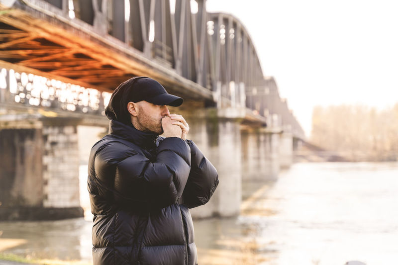 Man standing against bridge in city during winter