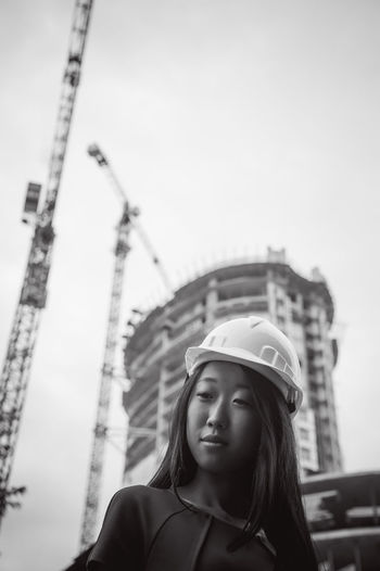 Low angle view of young woman standing in city against clear sky