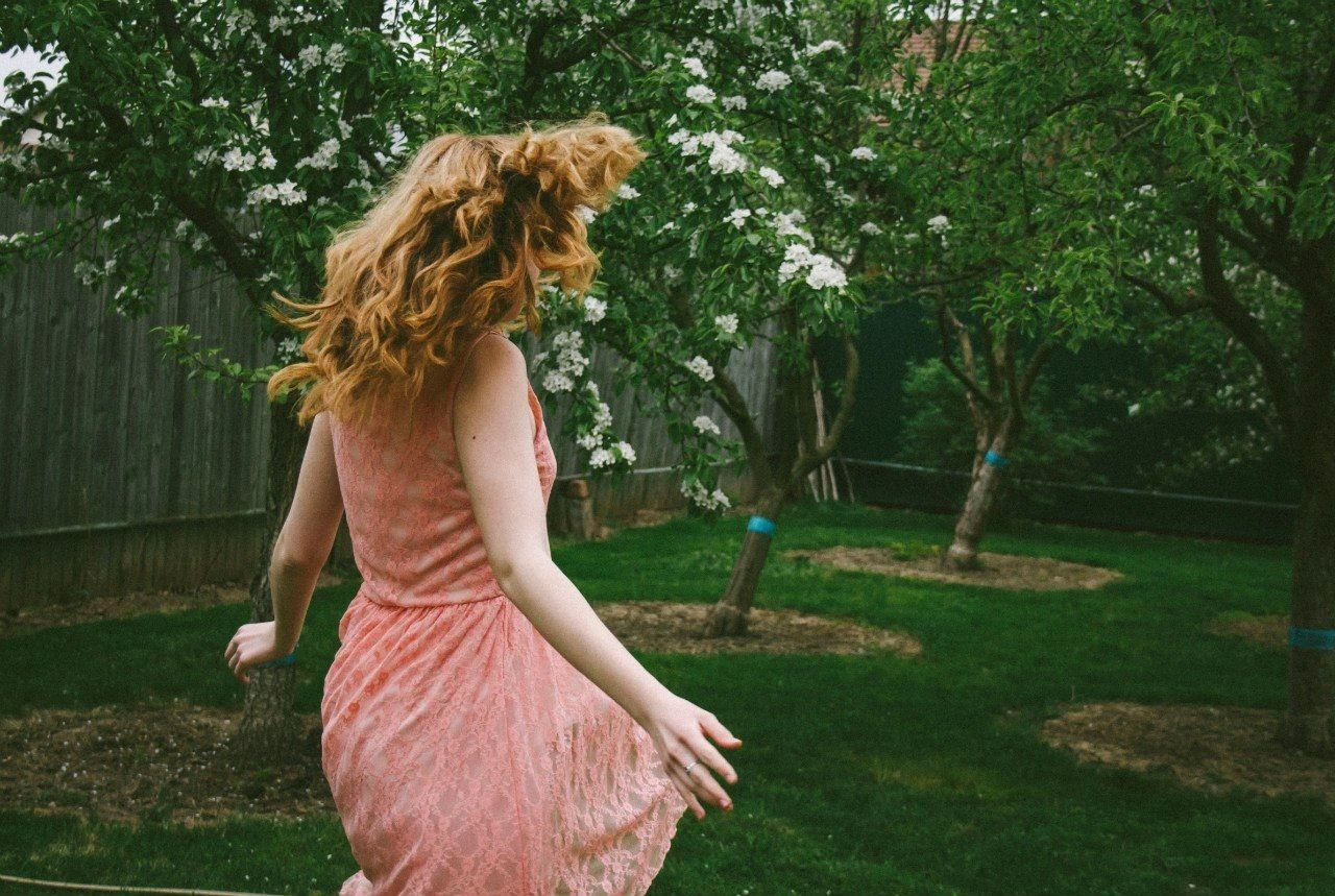 Side view of woman tossing hair in the lawn