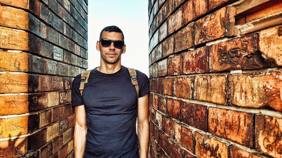 Man between bricks Portrait Zemun Belgrade Serbia Guy Young Adult City Men Standing Beard Looking At Camera Eyeglasses  Front View Mid Adult Sunglasses Brick Brick Wall Hands In Pockets Security Fence The Modern Professional