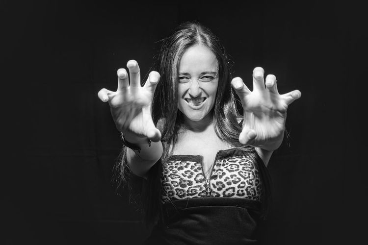 Portrait Of Woman Gesturing While Standing Against Black Background