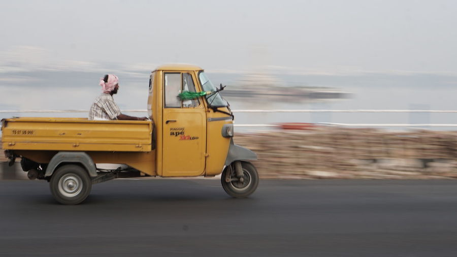 An Adult man sitting on Auto truck ,Panning Photography Outdoors Transportation Car Beach Full Length Day Yellow Vacations One Person Adult Sky One Man Only People Adults Only Only Men Nature EyeEm Panning Panningphotography Nwin Photography Sony Alpha Photography Sony A6000 Panning Hyderabaddiaries Sonyalpha Yellow Color