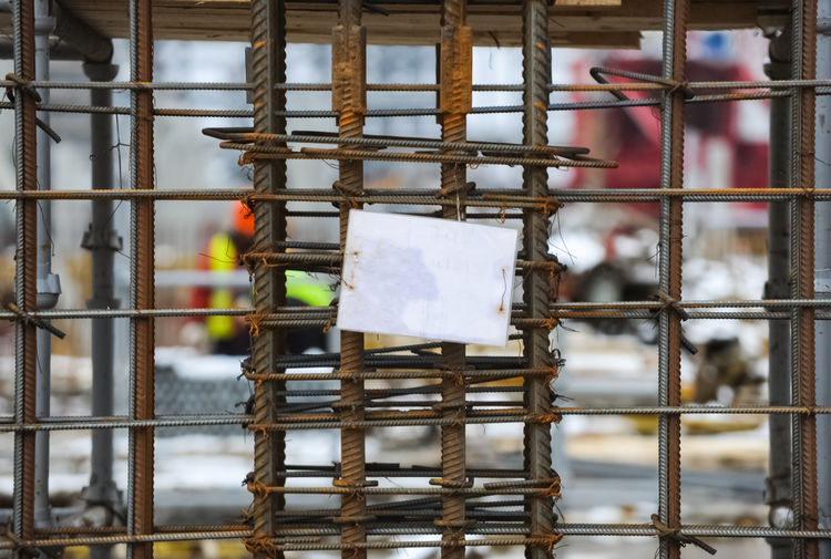 Space for writing on a white sheet of paper attached to steel reinforcement Day Metal No People Focus On Foreground Hanging Outdoors Paper Architecture Built Structure Occupation Wall - Building Feature Holding Communication Selective Focus Construction Industry Building Wood - Material