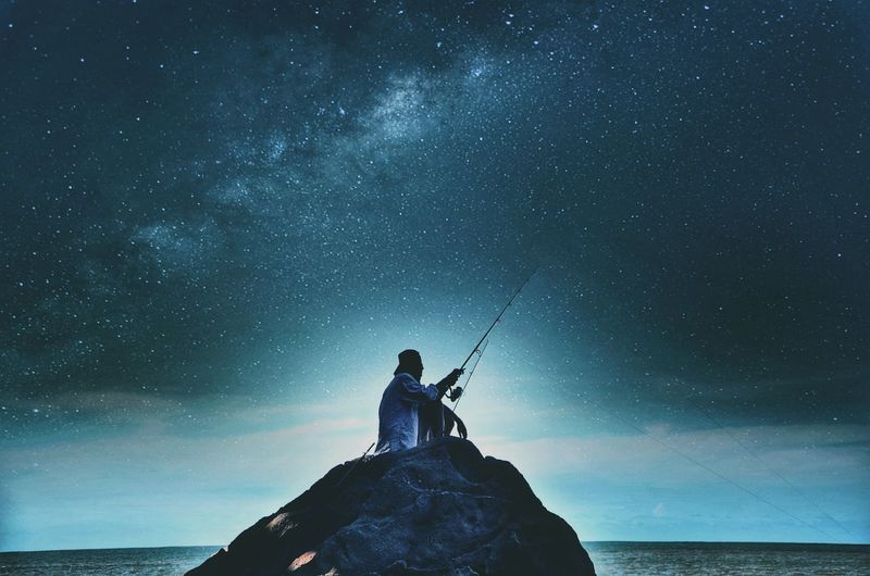Low angle view of man with umbrella against sky at night