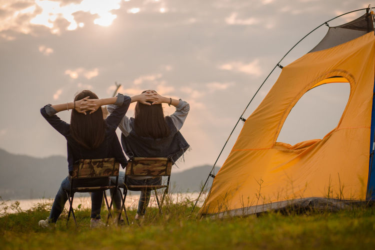 Men in tent on field against sky during sunset