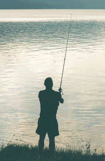 Enjoyment Escapism Fishing Full Length Getting Away From It All Hobbies Leisure Activity Lifestyles Light Men Nature Outdoors Real People Recreational Pursuit Sea Sitting Standing Vacations Water Weekend Activities