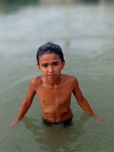 Portrait of shirtless boy swimming in water