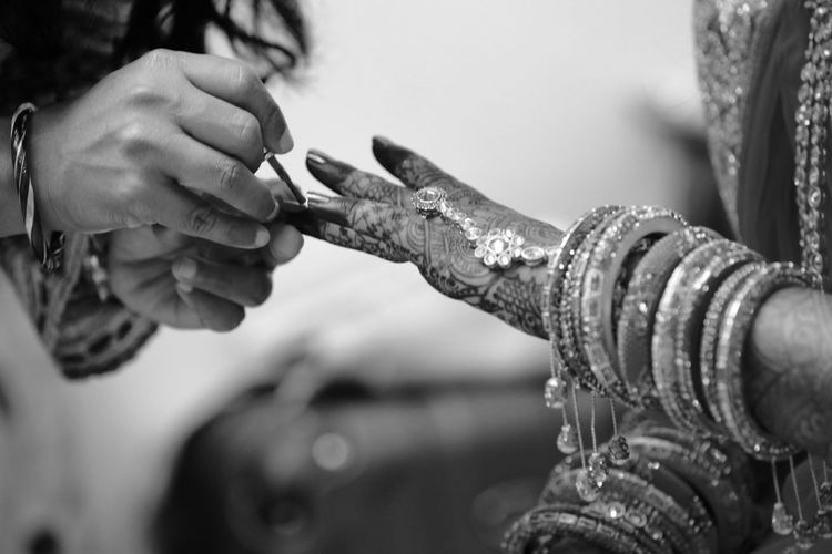 Close-up of woman applying nail polish on fingernails of bride