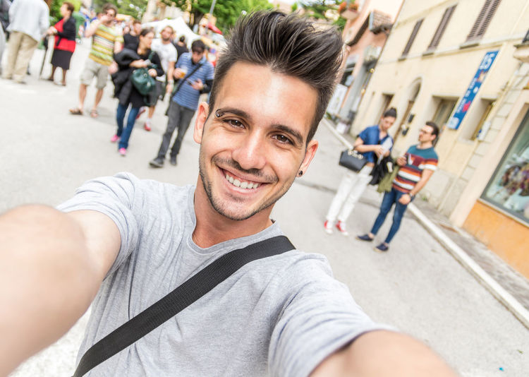 Portrait of happy young man standing on street in city