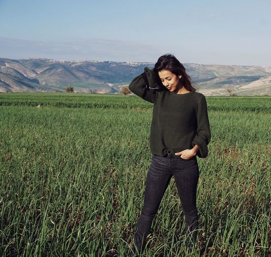 Young woman with hand in hair standing on agricultural field against sky