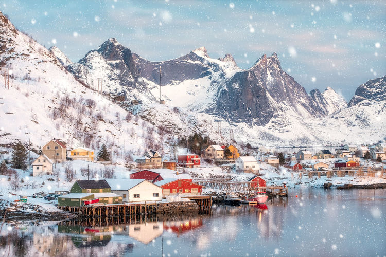 Colorful scandinavian village on coastline in snowing day at Reine, Lofoten islands, Norway Mountain Winter Cold Temperature Building Exterior Snow Architecture Building Water Built Structure Scenics - Nature Mountain Range Beauty In Nature House Reflection Snowcapped Mountain Nature Residential District Sky No People Outdoors Mountain Peak TOWNSCAPE