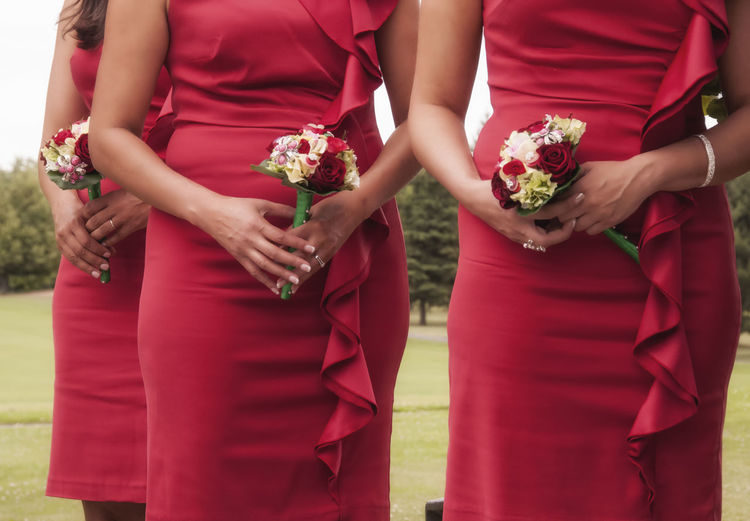 Midsection of bridesmaids holding bouquets in lawn