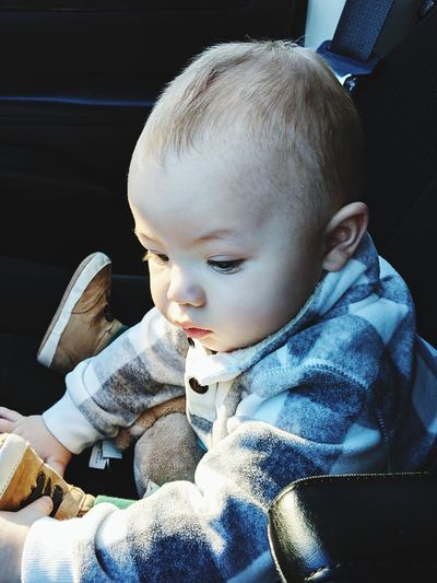 Close-up of cute baby boy sitting in car