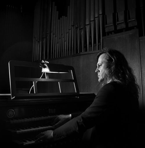 Side view of mature man playing piano