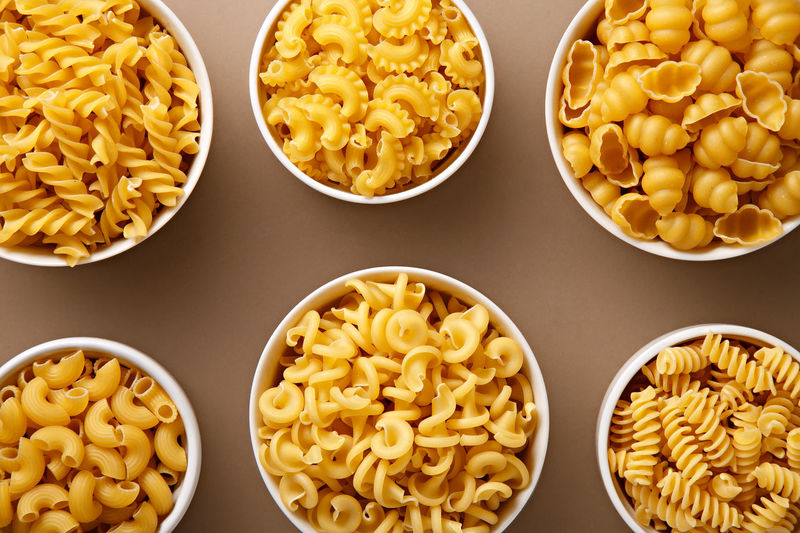 Pasta variations in bowls. Top view of raw Italian pastas (fusilli, conchiglie, pipe, elicodali, creste di galo Background Close Up Close-up Cooking Dry Food Freshness Full Frame Group Of Objects Ingredient Italian Food Meal Mediterranean  No People Pasta Pile Raw Uncooked Vegetarian Food Wheat Yellow