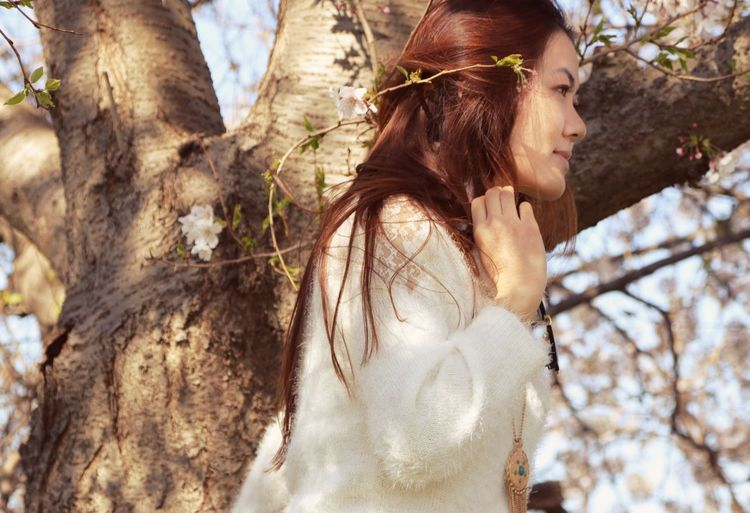 Young woman looking at tree trunk