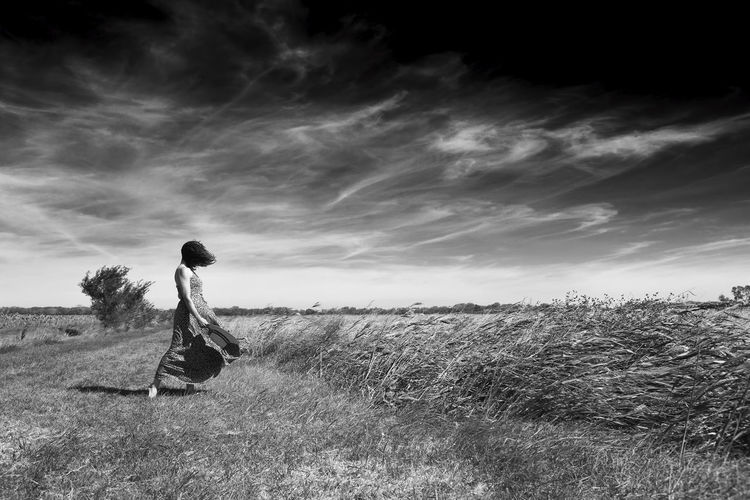 Side view of woman on field against sky