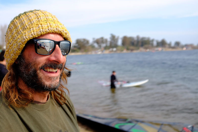 Close-up of smiling man wearing sunglasses against lake