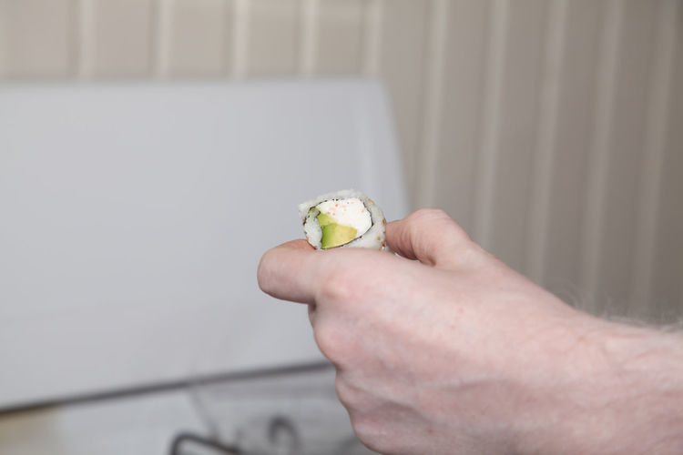 Close-up of hand holding ice cream against wall