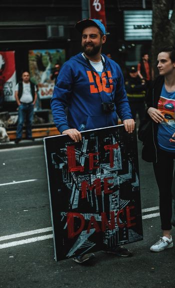 Man Holding Poster While Standing With Woman On Road
