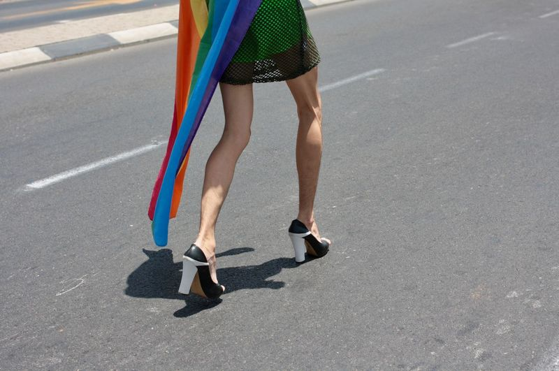 Low Section Of Man With Rainbow Flag Walking On Road