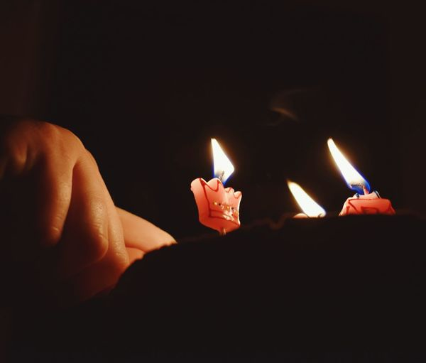 Close-up of hands burning candle