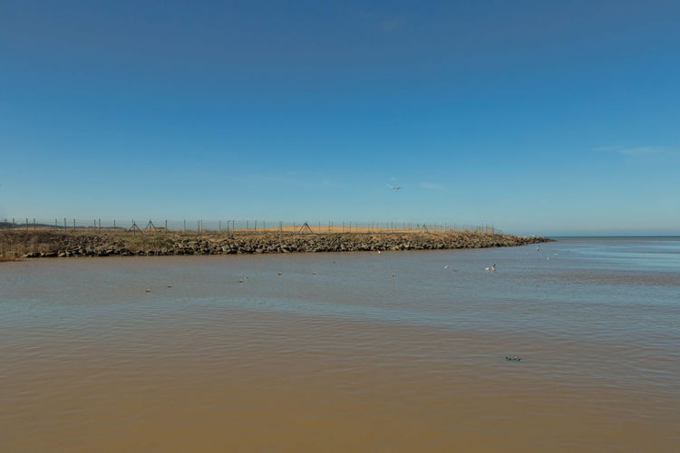 Scenic view of river against blue sky on sunny day