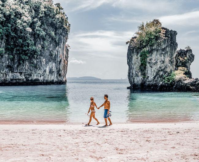 Men standing at beach against sky