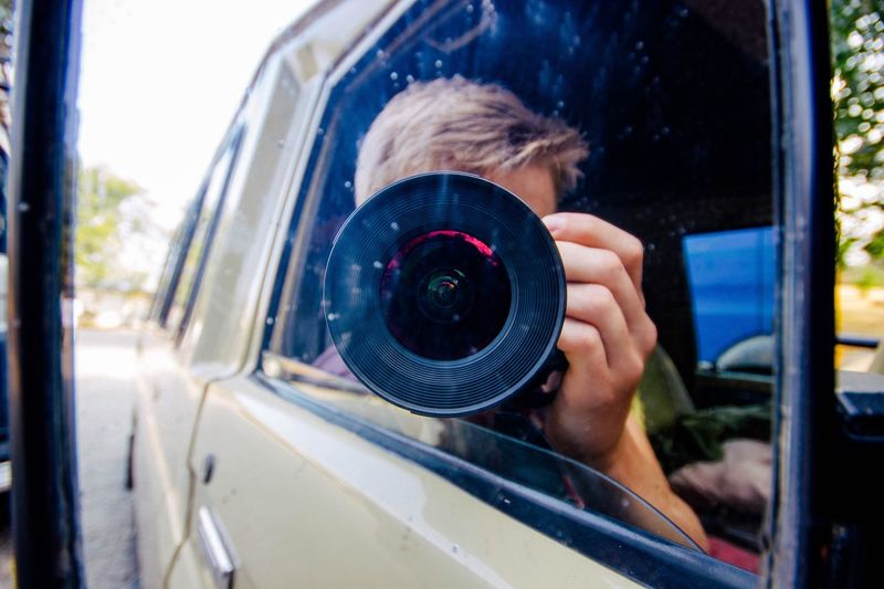 Reflection Of Man With Camera On Car Side-View Mirror