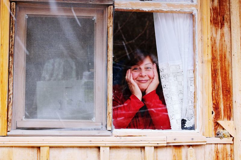 Portrait of smiling young woman looking through window