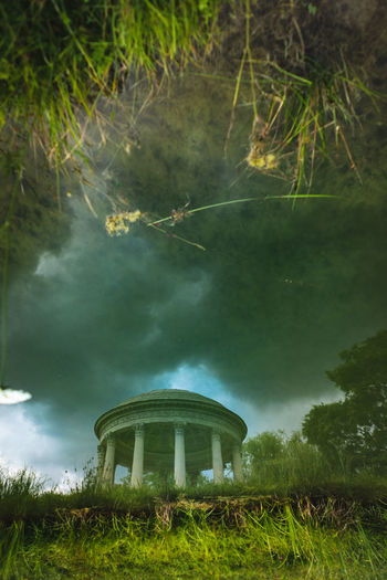 The Temple of Love in the gardens of Trianon. Queen Marie Antoinette's garden Pavilion at Versailles in France. Abstract view of abstract times. Abstract Photography Temple Of Love Architecture Beauty In Nature Building Exterior Built Structure Cloud - Sky Day Grass Green Color Growth Land Nature No People Outdoors Plant Reflection Sky Tranquil Scene Tranquility Tree Up Side Down Water