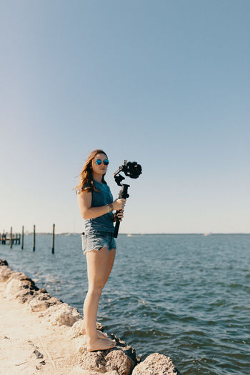 Woman photographing sea against clear sky