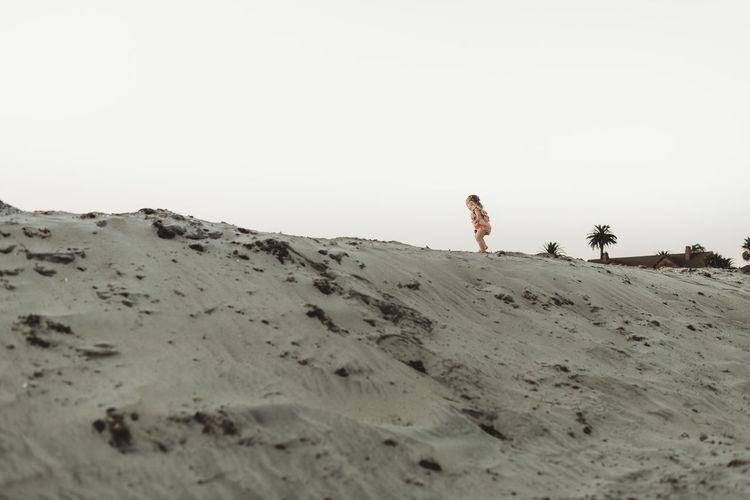 Man standing on desert against clear sky