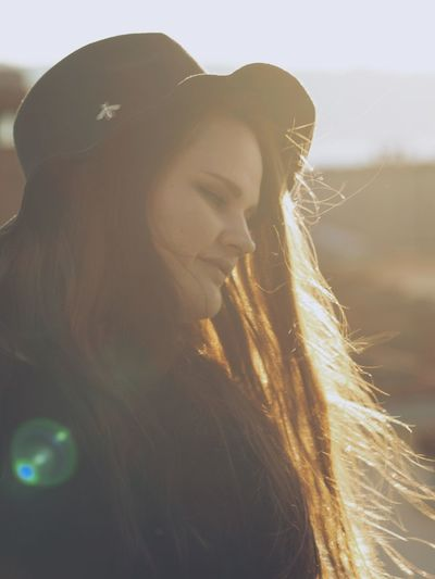 Side View Of Smiling Young Woman Wearing Hat During Sunny Day