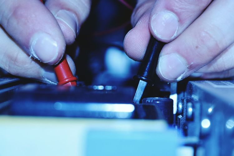 Close-up of human hand testing electronics