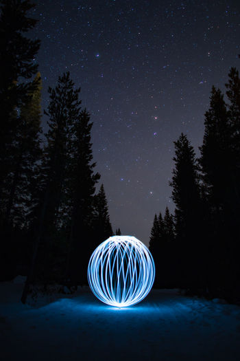 Illuminated light painting on snow covered field against sky at night