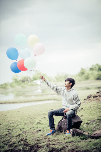 Balloon Casual Clothing Day Field Focus On Foreground Full Length Holding Land Leisure Activity Lifestyles Men Nature One Person Outdoors Real People Sitting Sky Smiling Young Adult Young Men