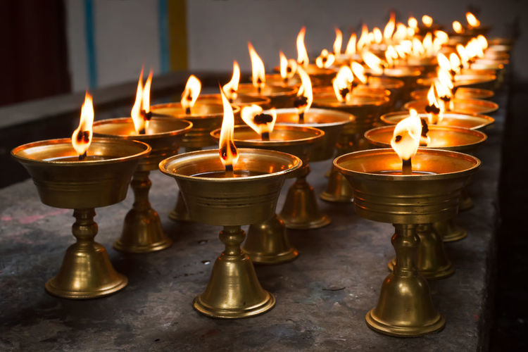 Close-Up Of Lit Diyas In Temple