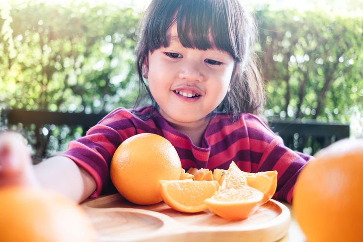 Fruit and Vegetable for Kids Concept. Little Cute 3-4 Years Old Girl with Sliced Orange on Wooden Plate. Fresh Juicy Fruit in Summer Orange Summer Kids Asian  Happy Slices Cute Playful Concept Child Girl Smile Face Smiling Day Children Fun Little Lifestyle Portrait Joy Young Happiness Cheerful Playing Childhood 3 Years Plate Fruit Vitamin Food Sliced Healthy Sweet Citrus  Natural Health Table Freshness Tropical Delicious Cut Juice House Home Outdoor Copy Space Eating Innocence Front View