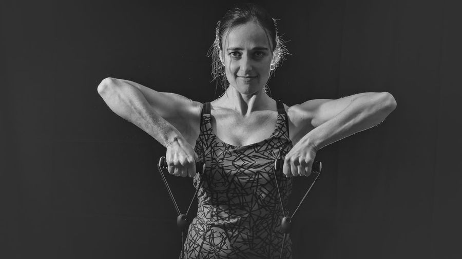 Portrait of woman exercising with resistance band against black background
