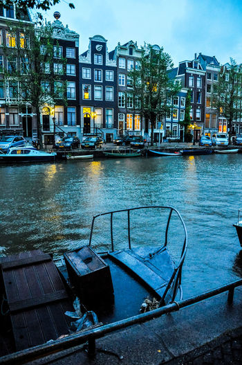 Boats moored in canal against buildings
